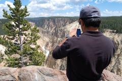 A person on a Yellowstone tour from Las Vegas takes pictures at Grand Canyon of the Yellowstone.