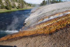 Thermal water pours from Excelsior Geyser into the Firehole River in Yellowstone.